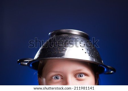Funny teen girl with a colander on her head. Half of the face - stock photo