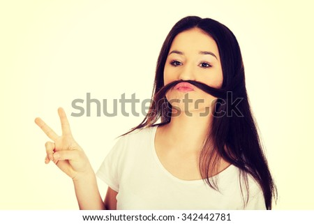 Funny teen woman putting hair like moustache. - stock photo
