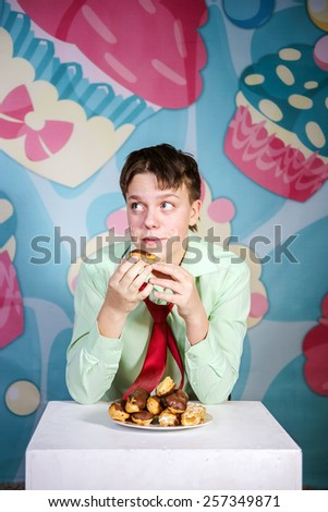 Funny teenage boy eating sweet cakes, hungry and candy man