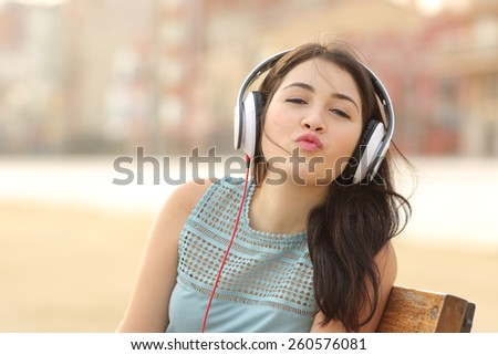 Funny teenager girl listening music with headphones kissing at camera - stock photo