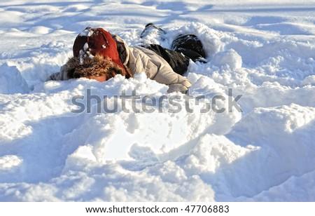 funny  teenager  girl lying in deep  snow - stock photo