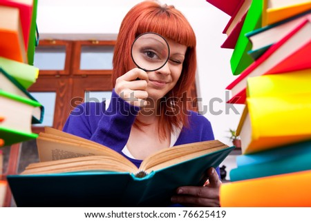 funny teenager searching something between pile of books - stock photo