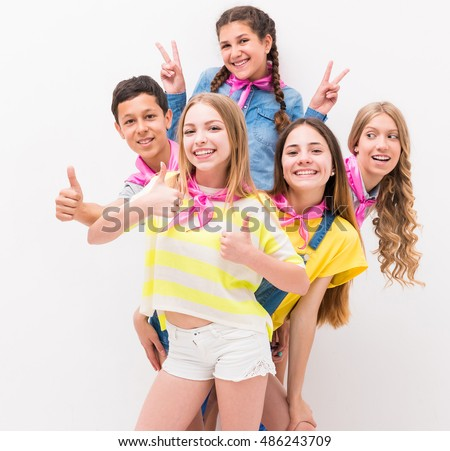 funny teenagers standing behind each other with gestures of peace