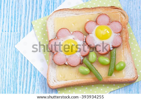 Funny toast with cheese, sausages, quail eggs and edamame