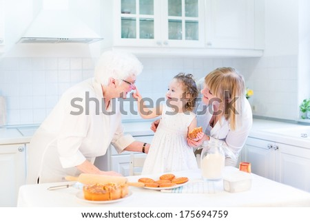 Funny toddler girl playing in a kitchen, having fun baking an apple pie with her grandmothers in a beautiful white sunny kitchen - stock photo