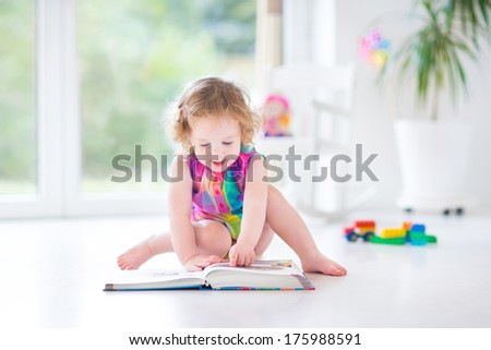 Funny toddler girl reading a book sitting on a floor in a white room with big garden view windows