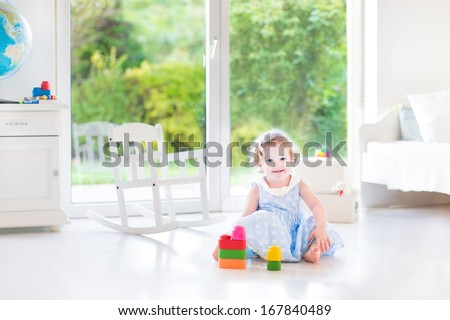 Funny toddler girl with curly hair wearing a blue dress playing in a white sunny bedroom with a big window with garden view  - stock photo