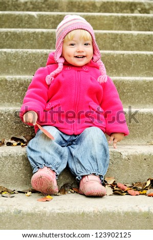funny toddler sitting on the stairs - stock photo