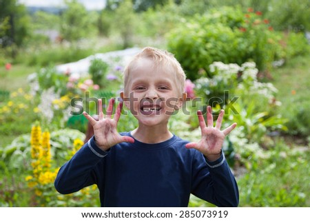 Funny toothless boy soiled by berries - stock photo