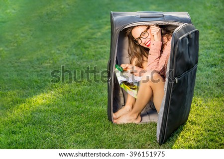 Funny traveler woman sitting in a huge suitcase and plan her trip holding map - stock photo
