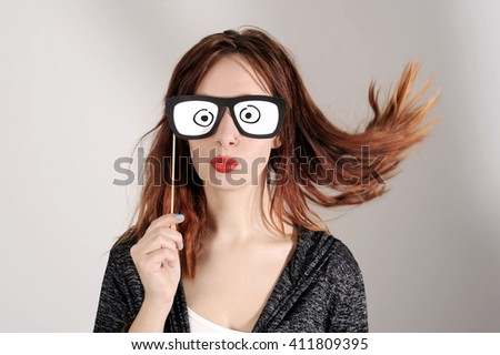 funny trendy fashion girl with paper glasses playing with emotion - stock photo