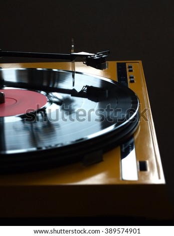 Funny turntable in yellow case with rotation vinyl record with red label isolated on dark background. Vertical photo front view closeup - stock photo