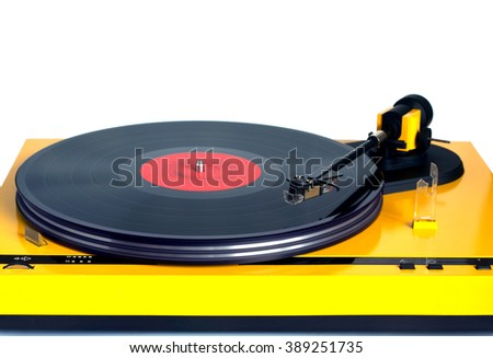 Funny turntable in yellow case with rotation vinyl record with red label isolated on white background. Horizontal photo front view closeup - stock photo