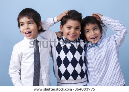 Funny twins are enjoying the day with their best friend in front of a blue background while they should be ready to go to the school. - stock photo