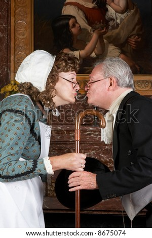"""Funny victorian scene of a husband leaving for work, kissing his wife goodbye. Shot in the old Castle """"Den Brandt"""" in Antwerp, Belgium (with signed property release for the castle interiors) - stock photo"""