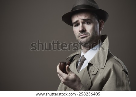 Funny vintage investigator in trench coat holding a pipe - stock photo