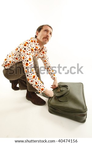 funny vintage young man looking in his suitcase - stock photo