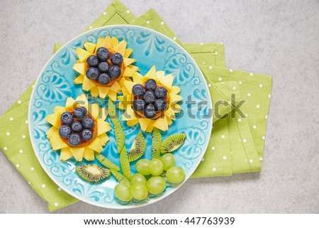 Funny wafer sunflowers with kiwi, grape, peaches and blueberry - stock photo