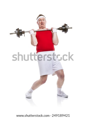 Funny weak body builder tries to lift a weight. Studio shot on white background. - stock photo