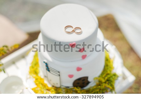 Funny wedding cake from mastic with a cup of milk and cookies. White wedding cake with flowers.  - stock photo