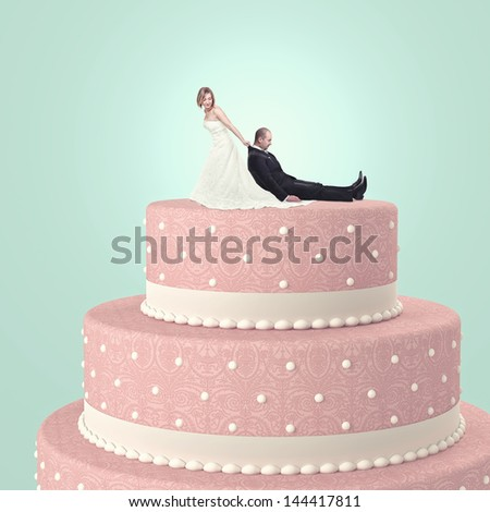 funny wedding cake with goom and bride - stock photo