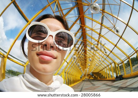 Funny wide angle portrait of a young woman in sunglasses