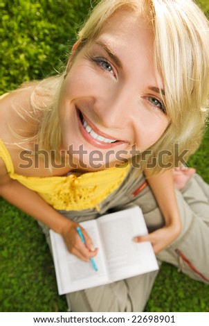 Funny wide angle portrait of a young woman reading book outdoors