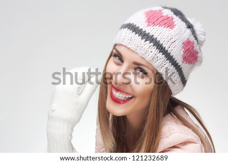 Funny winter portrait of young smiling woman in a wool hat on light background - stock photo