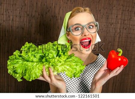 Funny woman cook holding salad and sweet pepper, close up of a housewife - stock photo