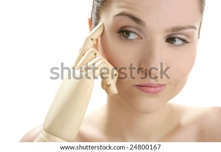 Funny woman cosmetic portrait, thinking with mannequin wooden hand - stock photo