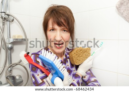 funny woman holding brushes ready to wash bathroom shower