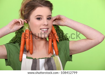 Funny woman holding carrots to her ears - stock photo