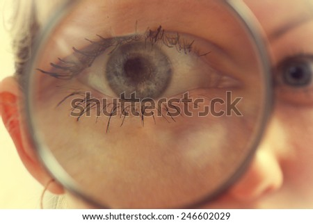 Funny woman looking through a magnifying glass - stock photo