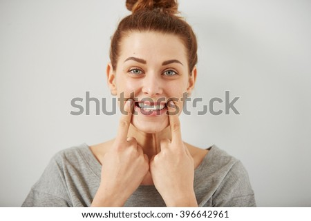 Funny woman on grey background. Cheerful female model joyful. Positive human emotion facial expression body language.  - stock photo