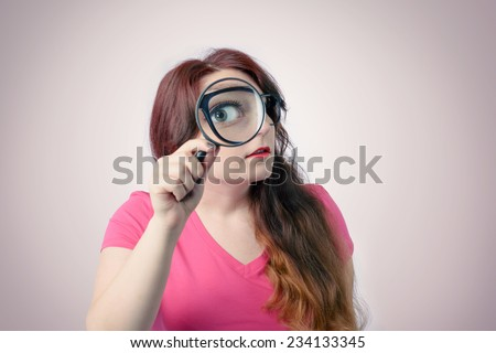 Funny woman using magnifying glass. Big zoom concept - stock photo