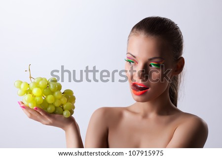 Funny woman with glow make-up and green grapes - stock photo