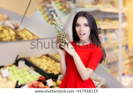 Funny Woman with Pineapple Fruit in Supermarket - Young girl looking for best vegetarian ingredients in a grocery store  - stock photo