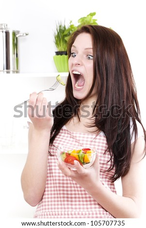 funny woman with wide open mouth and eyes  eating salad - stock photo