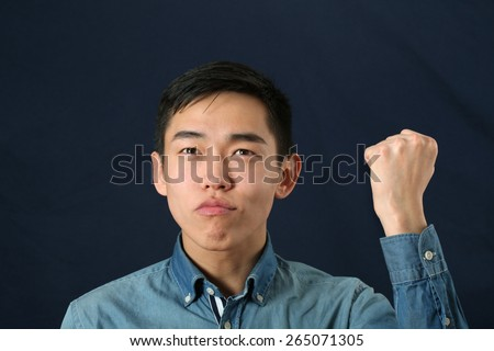 Funny young Asian man shaking his fist and looking upward - stock photo