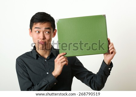 Funny young Asian man showing green copy space box and looking sideways - stock photo