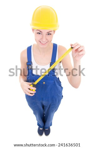 funny young attractive woman builder in workwear with measure tape isolated on white background - stock photo