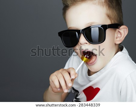 Funny Young Boy Eating A Lollipop.Fashionable child in sunglasses - stock photo
