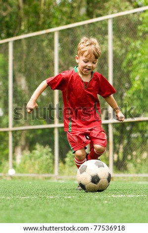 Funny young caucasian boy with soccer ball