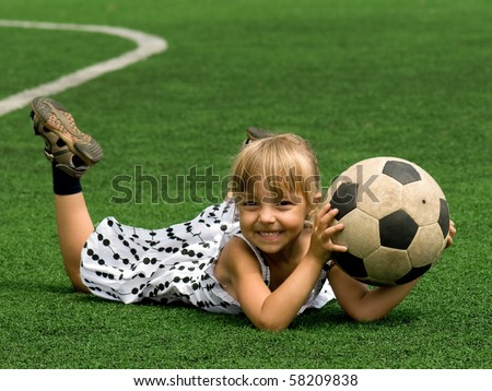 Funny young caucasian girl with soccer ball - stock photo