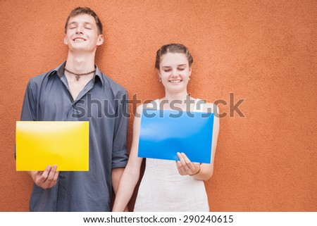 Funny young couple close eyes and thinking of something pleasant, what gift they would like to receive! They holding yellow, blue frame or card at red background. World Kissing Day or Valentine's Day - stock photo