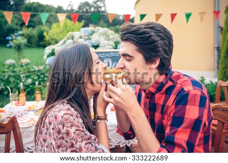 Funny young couple laughing and eating an american hot dog in a outdoors summer party - stock photo