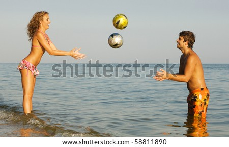 Funny young couple playing balls on the beach - stock photo