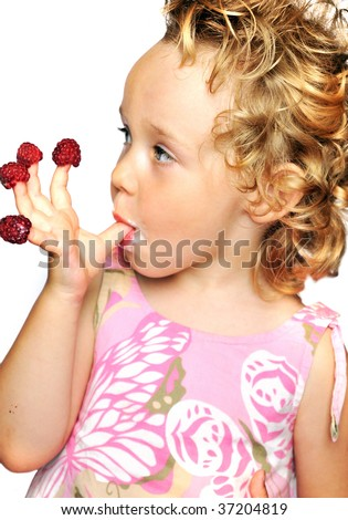 funny young girl enjoying a fresh raspberries stacking on her fingers - stock photo