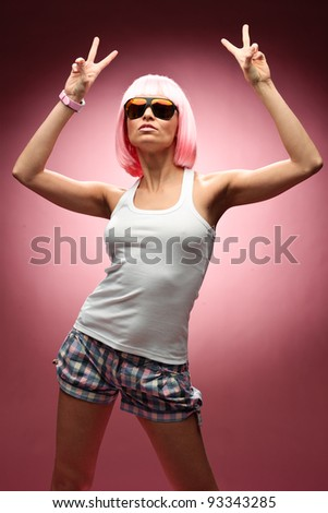 Funny young girl in pink wig and glasses dancing for camera across pink background - stock photo
