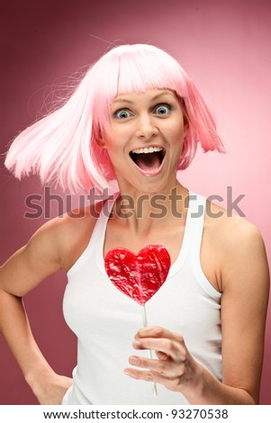 Funny young girl in pink wig holding lollipop and posing for camera across pink background - stock photo
